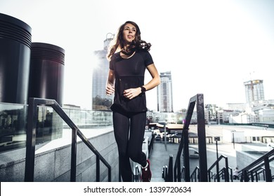 Young Woman running upstairs against urban background