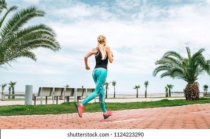 Young woman runs on the sea embankment. Active life style