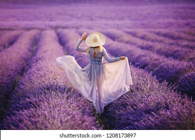 Young woman runs in purple lavender field sunset. Dress and hat develop wind. France, Provence.