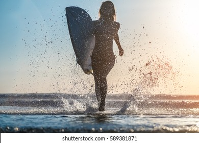 Young woman runs with surfboard with lots of splashes
