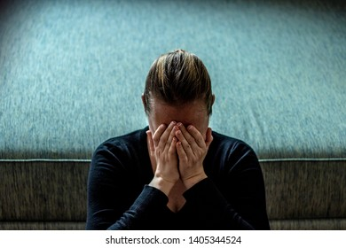 Young woman sad and fear stressful depressed emotional. Stop abusing violence in women. Portrait of a stressful women sitting on the floor with hands on her face.