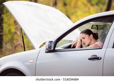 Young woman sad in her car because she broke