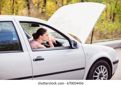 Young woman sad in her car because it broke