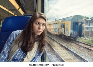 The young woman sadly looking out the window sitting inside the train car.