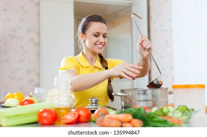 young woman salts the soup in the pan