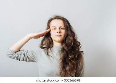 Young woman salutes, the hand to the head. On a gray background.