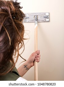 Young woman is sanding wall with pole sander before painting in house under remodeling