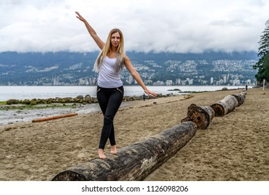 Young woman at the sandy beach of Stanley Park stands barefoot on log, her arms are raised and doing some acrobatic exercise movement, Vancouver, British Columbia, Canada