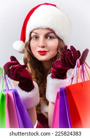 young woman in Santa Claus costume holds shopping bags