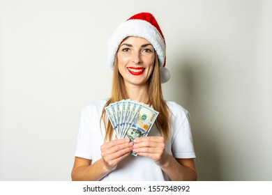 Young woman in a Santa Claus hat is holding a bundle of money in his hands on a white background. Christmas sale concept, black friday, discount, rich, win, bet