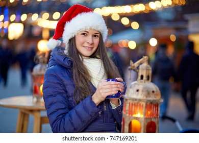 Young woman with santa hat drinking mulled wine on Christmas Market
