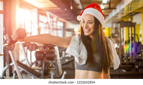 Young woman in Santa hat with dumbbells at gym. New Year. Christmas, holidays, fitness, and gym concept.