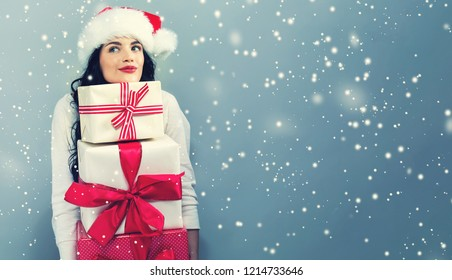 Young woman with santa hat holding gift boxes on a gray background
