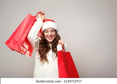 b18df0c2644fc Young woman in santa hat with shopping bags on grey background