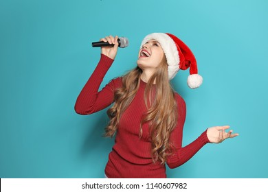 Young woman in Santa hat singing into microphone on color background. Christmas music