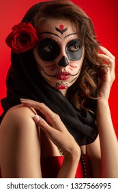 young woman with santa muerte makeup on red background