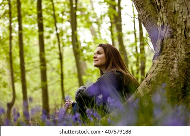A young woman sat against a tree trunk in a field of bluebells