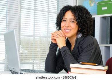 Young Woman Sat At Her Desk Using A Laptop Computer