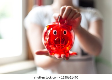 Young woman saves money in a red piggy Bank