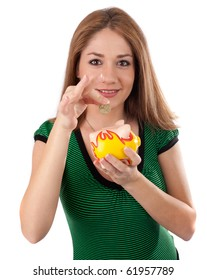 Young woman saving money in a piggybank,isolated on white