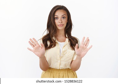 Young woman saying no, dislikes offer. Attractive stylish female raise hands in rejection, make skeptical reluctant expression, asking stop, unwilling continue conversation, having disagreement
