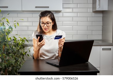 Young woman scared and holding a credit card and your smartphone