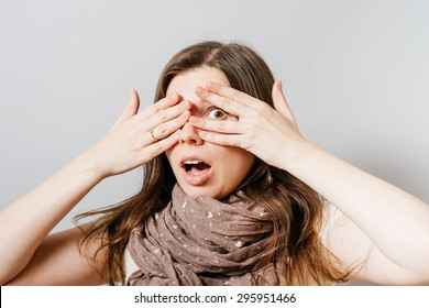 A young woman scared, looking through her fingers. On a gray background.