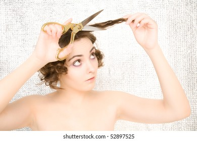 Young woman with scissors cutting her hair