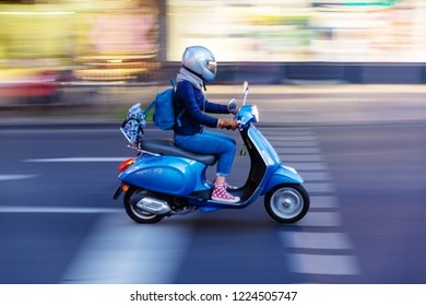 young woman with a scooter on the move in the city with motion blur effect