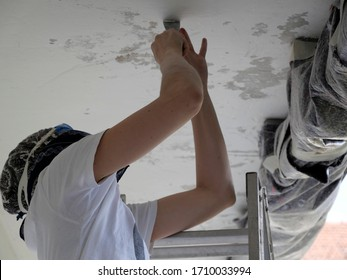 Young woman scraping peeling paint off a ceiling do it yourself