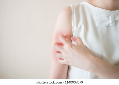 Young woman scratching arm from having itching on white background copy space. Cause of itchy skin include insect bites, dermatitis, food/drugs allergies or dry skin. Health care concept. Close up.
