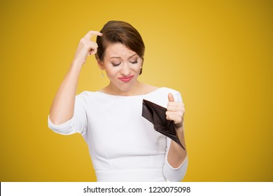 Young woman scratching in head and looking inside of empty wallet having no money