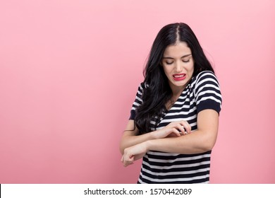 Young woman scratching her itchy arm on a pink background
