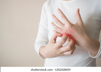 Young woman scratching the itch on her hands w/ redness rash. Cause of itchy skin include dermatitis (eczema), dry skin, burned, food/drugs allergies, insect bites. Health care concept. Copy space.