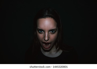 Young woman screaming in the dark