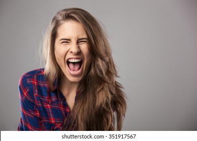 Young woman screaming loudly - studio portrait.