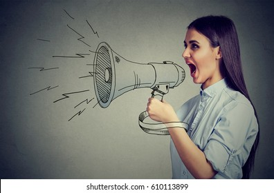 Young woman screaming in megaphone isolated on gray wall background. Negative face expression emotion feelings. Breaking news, power, social media communication concept