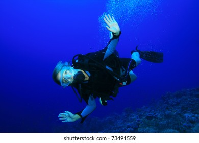 Young woman scuba diving in clear tropical sea