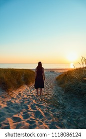 Young woman at the sea enjoys the sunset