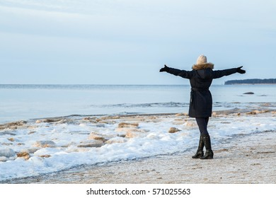 Young woman at the seaside feels the freedom in winter afternoon.