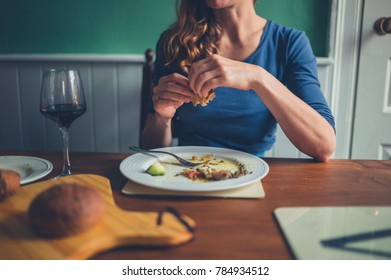 A young woman is seated at a table and is eating a meal of bread and wine