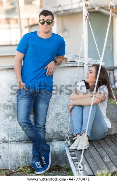 Young woman seating on a wood floor and young man standing next to her