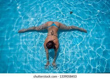 The young woman in the seductive bikini lies in the pool in a splits. Girl in mini bikini gymnast in the pool