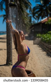 A young woman in a seductive bikini stands under an outdoor shower. The girl washes away the salt water under the shower by the sea