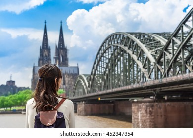 Young woman seen from back looking to rhine river, huge bridge and famous cathedral of Cologne, Germany/Tourist View to Cologne