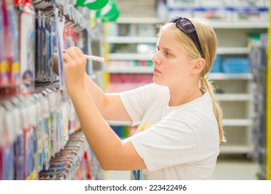 Young woman select writing tools in stationery department in supermarket
