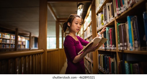 Young woman selecting book in library at college