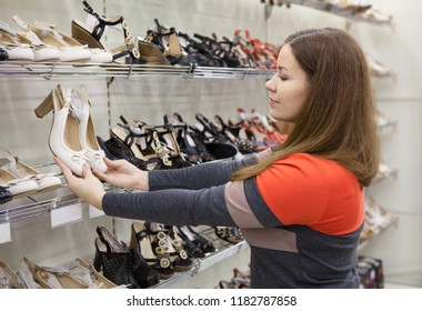 Young woman selecting new shoes in store, holding hands barefoot slippers