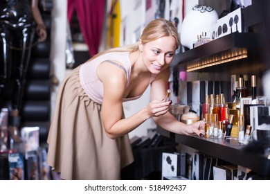 Young woman selecting pheromones cologne in sex shop