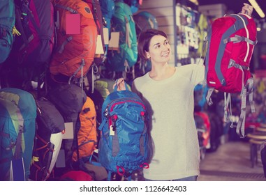 Young woman selects a tourist  rucksack in the store